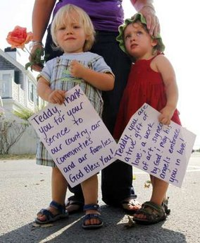 """Children outside te Kennedy home with a sign that reads """"Teddy, thank you for your service to our country, our communities and our families.  God bless you!"""
